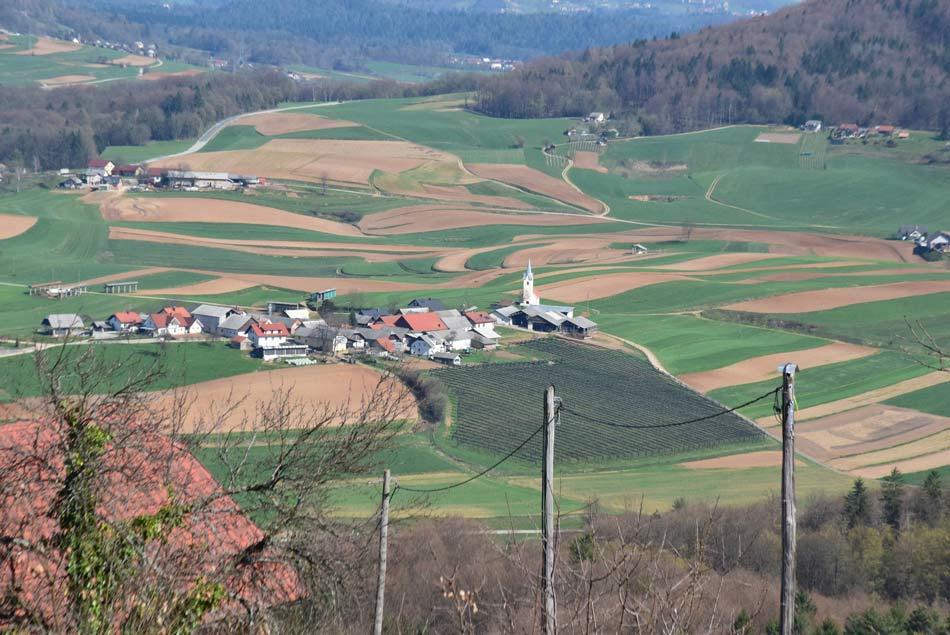 Tipična vasica stisnjena med travniki in njivami.
