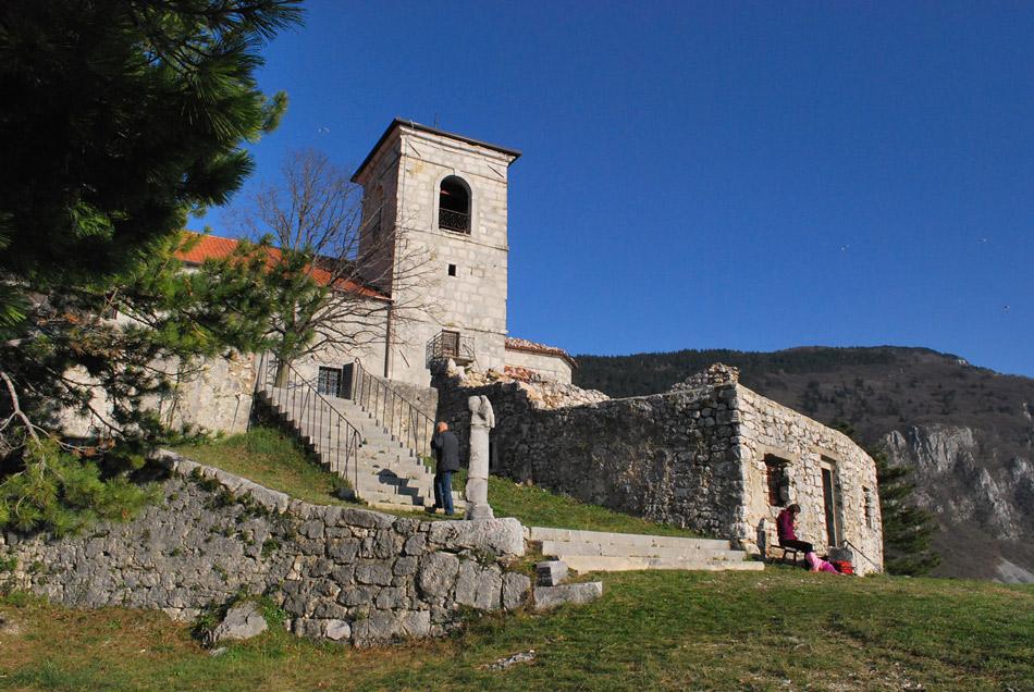 Vitovska cerkev in za njo Trnovski gozd.
