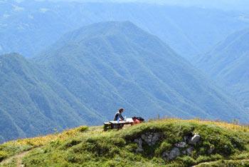 Na Črno prst se lahko povzpnemo mimo Orožnove koče na Planini za Liscem in se krožno vrnemo preko planina Osredki. Na sliki planinec malica pod Domom Zorka Jelinčiča.