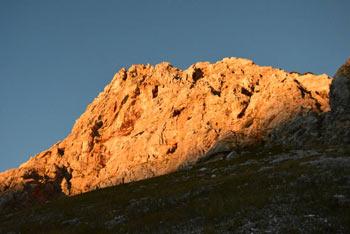 Od sonca ožarjena stena Male Tičarice visoko nad Kočo pri Triglavskih jezerih.