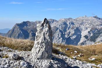 Kser je izvrsten razglednik na Spodnjih Bohinjskih gorah. Na sliki je ostanek mejnega kamna in v ozadju pobočja Krnskega pogorja nad dolino Tolminke.