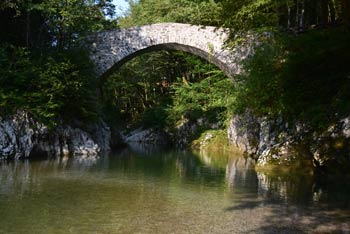 Napoleonov most ima visok kamniti lok, ki se pne nad zelenim tolmunom reke Nadiže.