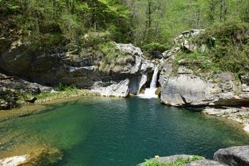 Reka Idrija se ponaša z velikim zelenim tolmunom v katerega pada nekaj metrov visok slap.
