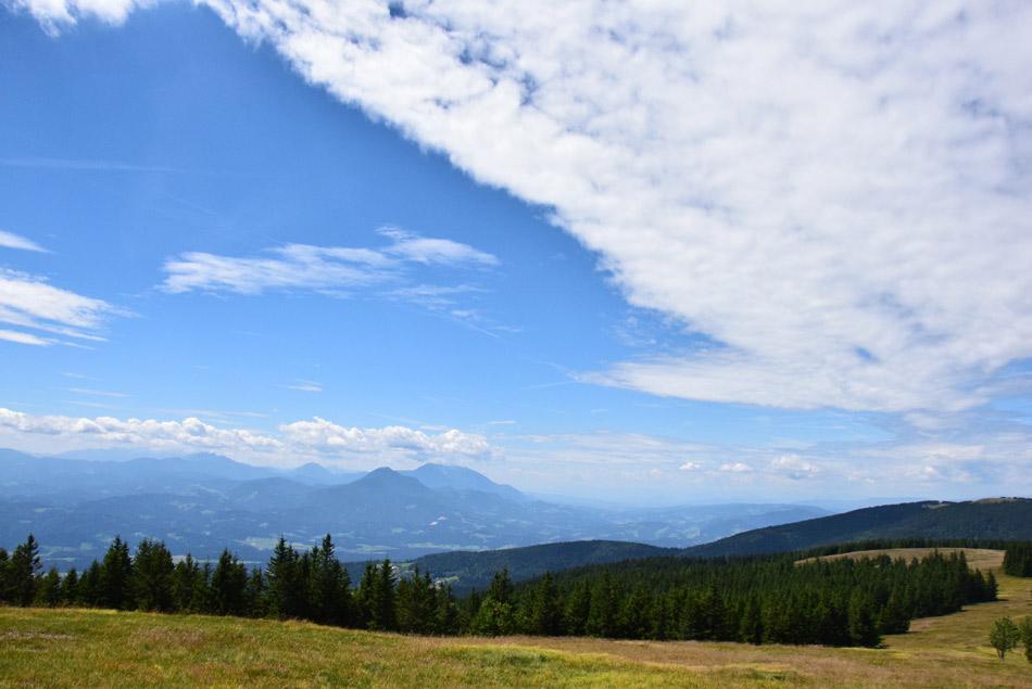 Spoj pohorskih prostranih travnatih pobočij z oblaki na nebu. V ozadju se vidi koroški Uršjo goro in Peco.