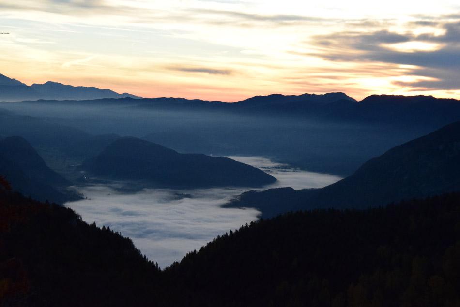 Bohinjsko jezero prekriva jutranja megla. Sončni vzhod na Komni.