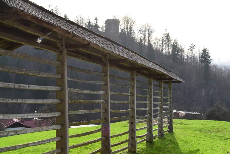 Pogled na Povšetov grad, oziroma tudi Vilo Kansky. Pred njim se nahaja lepo ohranjen kozolec v naselju Podgrad.